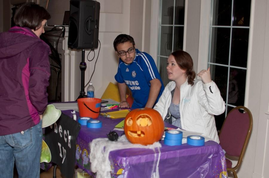 Students welcome local families to campus in the Fred Meyer Lounge at the check-in desk for the Trick-or-Treat Tour.