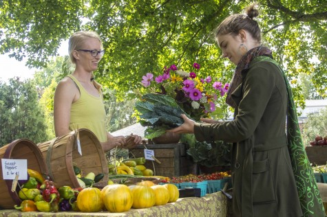 Spencer Beck/For the Review Freshman Alex Brown visits the Linfield Farmer's Market on Tuesday, Sept. 16, where Beth Satterwhite (left) from the Yamhill River Farm was selling locally grown fruits and vegetables such as kale, cherry tomatoes, melons and pears.