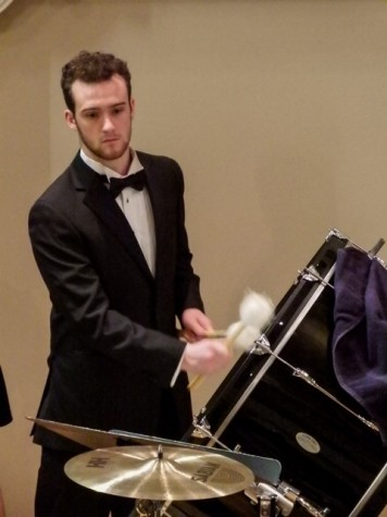 "Jeff Laws, '16, plays the drum in ""Cloudburst"" during the Linfield choir's  home concert on Wednesday, Feb. 24."