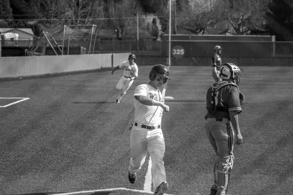 Joey Cassano, '18, (#25) running home with fellow Linfield 'Cat running in background to score two runs in a previous game.