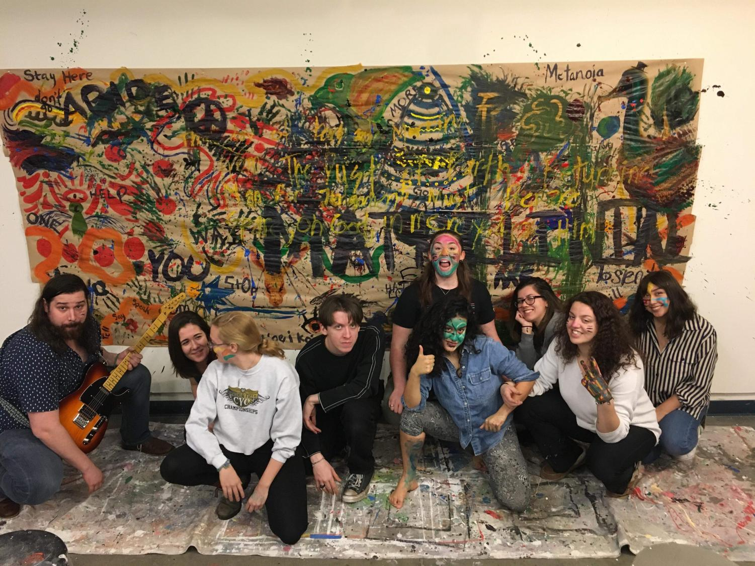 The friday night art group poses in front of their artwork, the result of a directive painting activity.