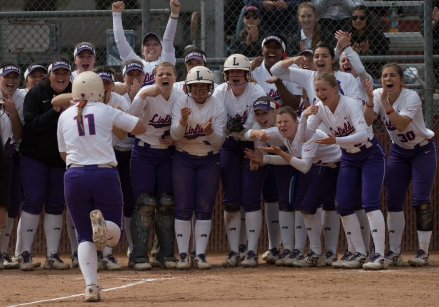 Team+celebrates+Paige+Smotherman%2C+%E2%80%9819%2C+running+home+after+jacking+a+2-run+homer+over+right-center+field%2C+making+the+score+7-0.%0A
