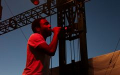 image of rapper Childish Gambino singing into mic in front of dark blue set