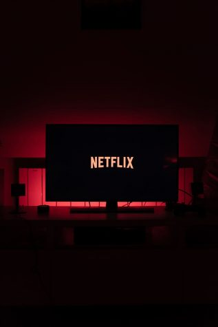 The red and white Netflix logo lights up a black flat screen tv screen in a dark room with red back lighting.