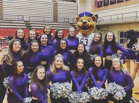 Photo of the ladies of the Linfield Dance Team in purple uniforms with silver pompoms with Mack the Wildcat in the Linfield gym.