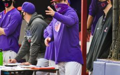 Coach Dan Spencer communicates with players on the field during Linfield baseball's home opener last weekend.