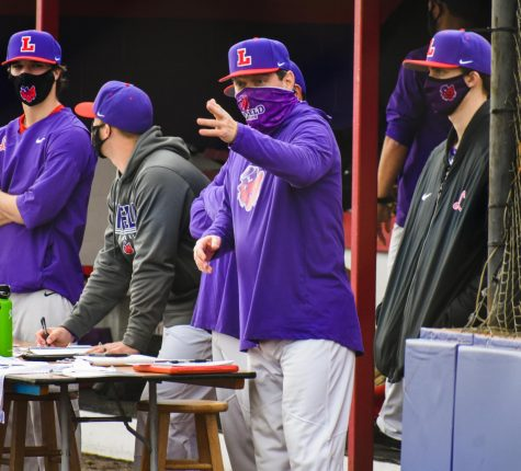 Coach Dan Spencer communicates with players on the field during Linfield baseball