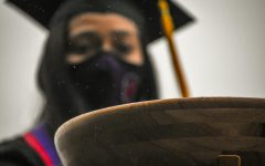 A graduating student drops her acorn back in the bowl.