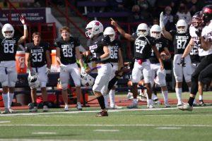 El estudiante de segundo año Connor McNabb corre con el balón hacia atrás para hacer un touchdown, mientras sus compañeros del equipo aplauden desde afuera del campo de fútbol.